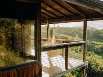 a treehouse in the hills of Hawaii with a hammock on a lanai