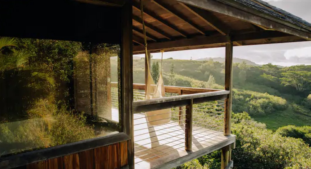 A treehouse in the hills of Hawaii with views of the mountains and a hammock on a lanai.