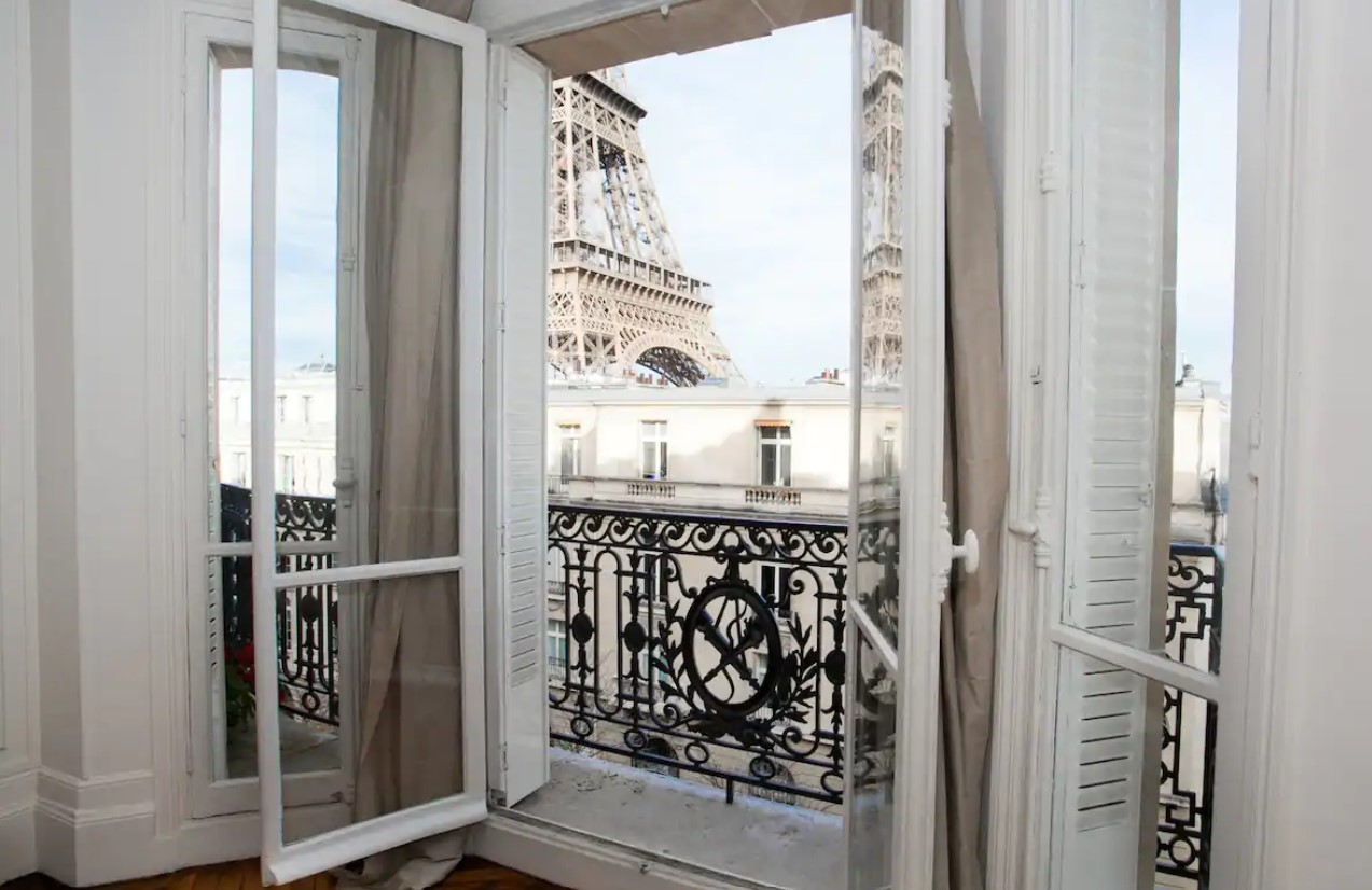 The view of the Eiffel Tower from the open French doors of a charming Paris Airbnb that leads to a private balcony