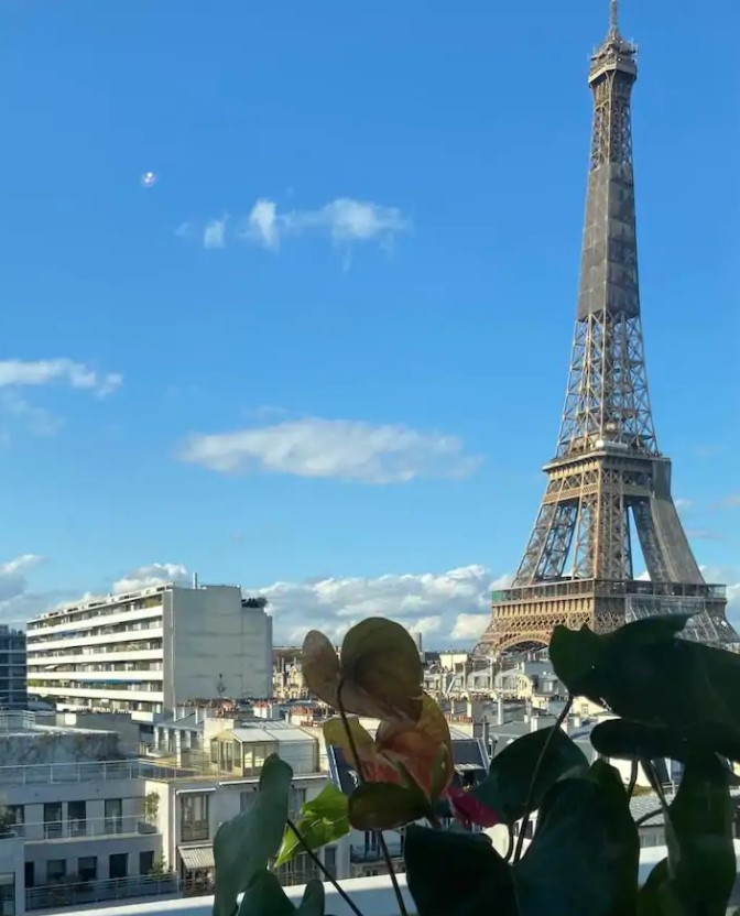 The view of the Eiffel Tower on a sunny day with blue skies from a small balcony