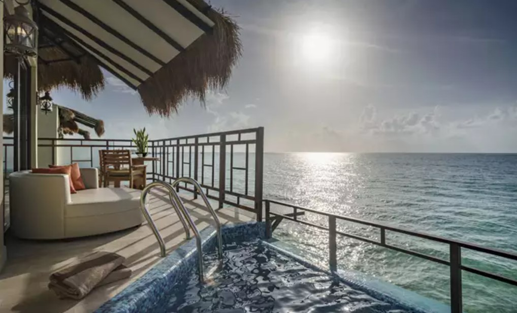 The deck of an overwater bungalow with a sun lounger couch, a bistro set, and a hot tub.