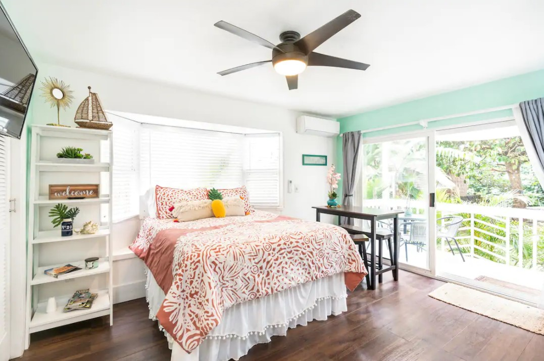 The inside of a studio apartment in Hau'ula Hawaii with a queen sized bed and large sliding doors that lead to a private lanai airbnbs in hawaii
