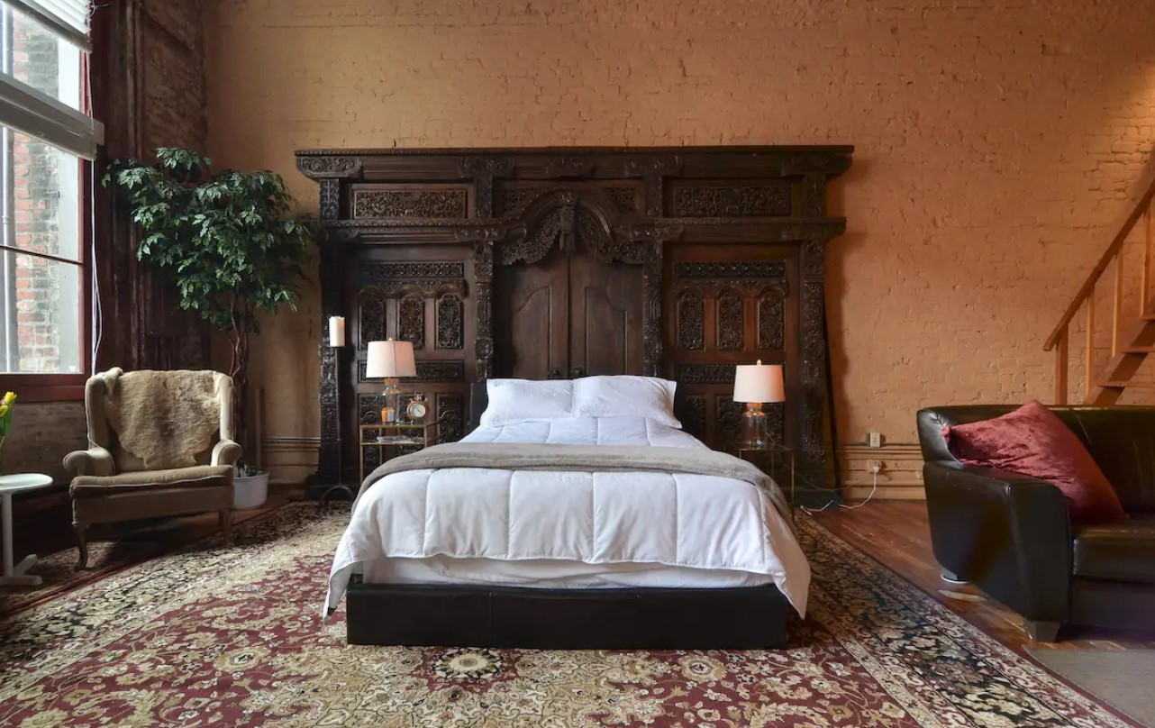 A large studio space with painted brick walls, large windows, and a large ornate wooden headboard behind a queen-sized bed in Seattle