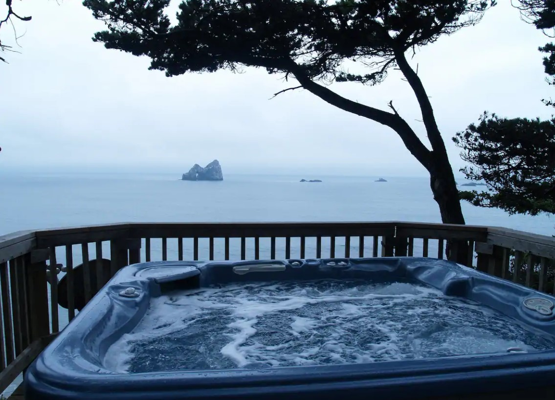 A private hot tub that looks out at a private beach and cove on the Oregon Coast