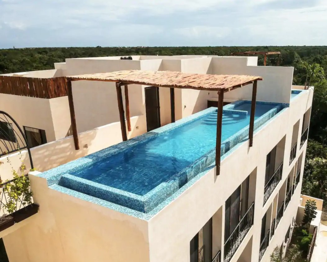 A large infinity pool at the top of an apartment building in mexico