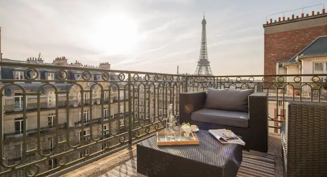 A large balcony with comfy seats and a view of the Eiffel Tower in the background