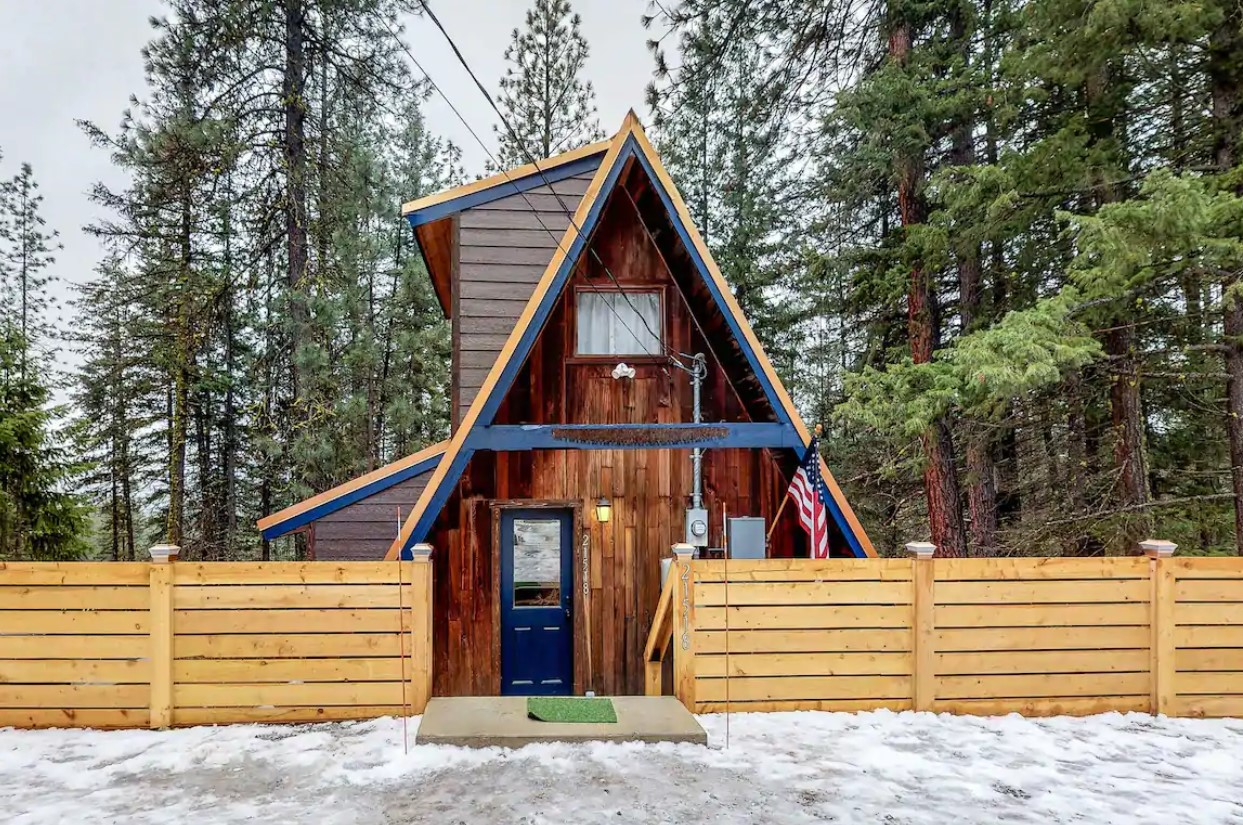 A large A-frame cabin in the winter with dense trees behind it and a privacy fence in front of it