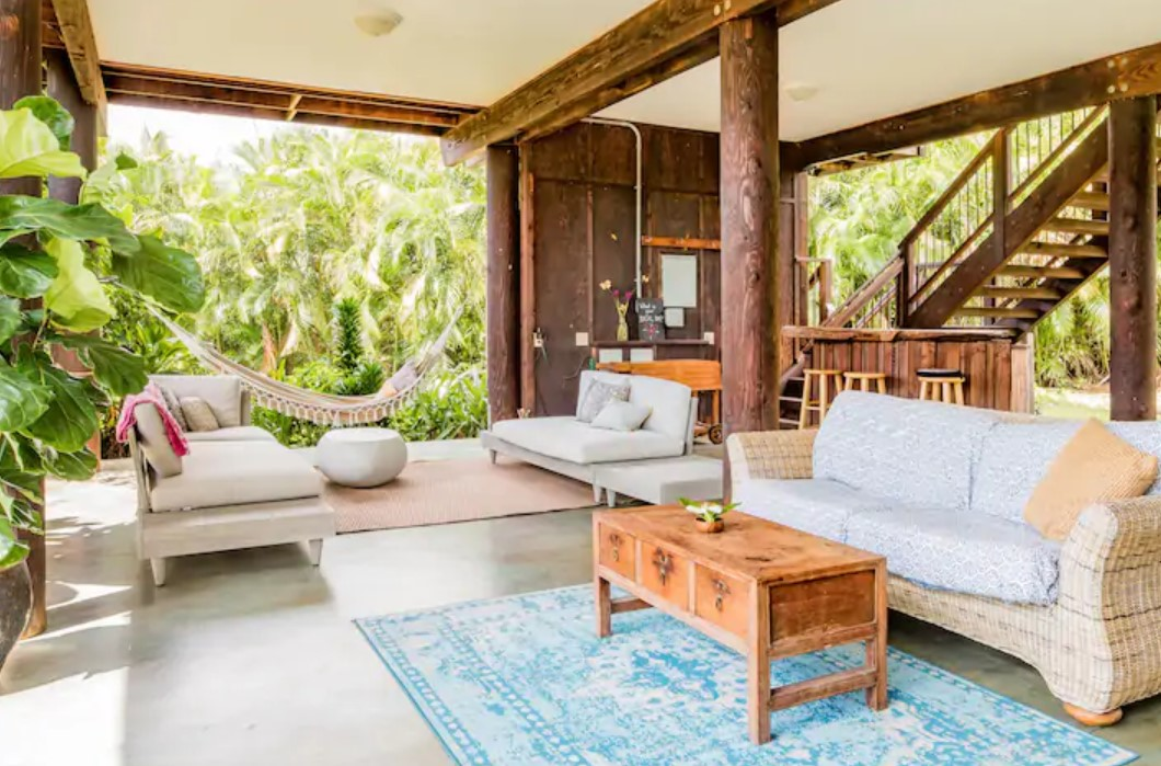Looking at an open air living space with two couches, a hammock, and a bar space surrounded by tropical greenery