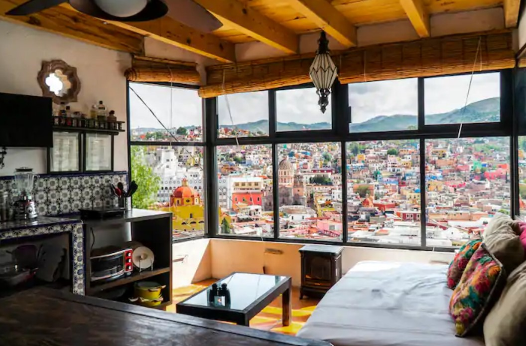 A small studio space with large windows that view a colorful Mexican cityscape best airbnbs in Mexico