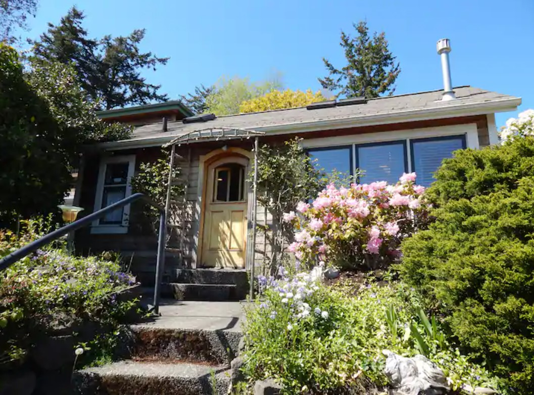 The exterior of a charming cottage surrounded by a beautiful garden in Port Townsend