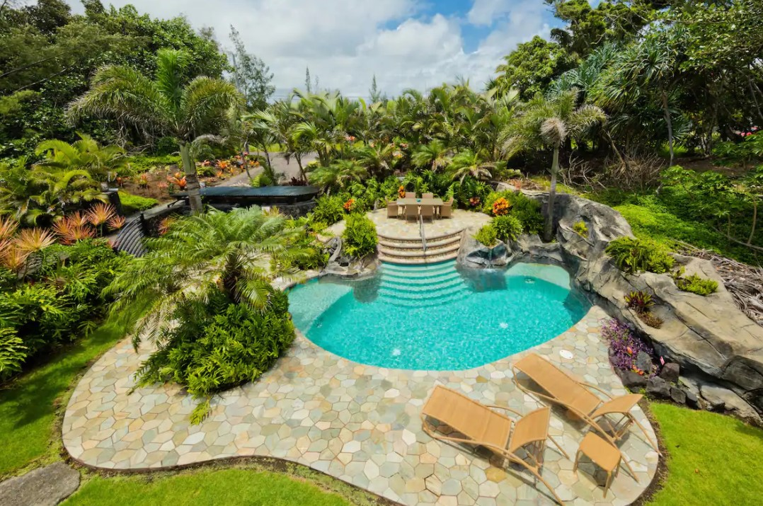 An aerial view of a large in ground pool surrounded by a stone patio and lush tropical greenery best airbnbs in Hawaii