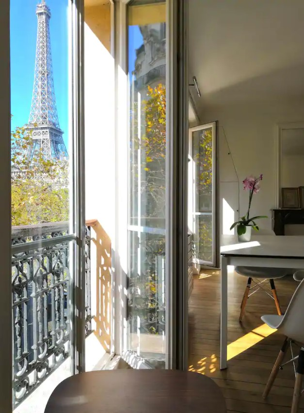 Looking through the side of a balcony door that leads to a small balcony with views of the Eiffel Tower