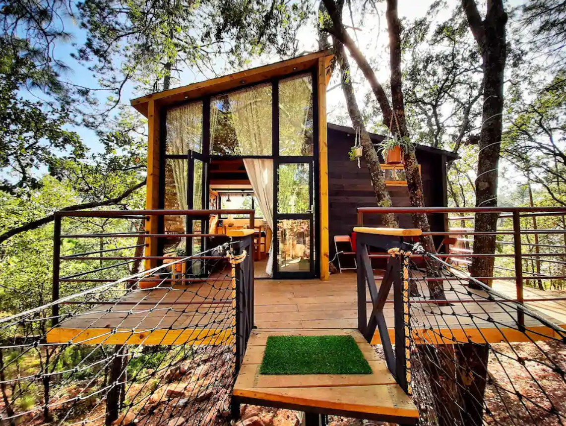 The exterior view of an elevated treehouse in the woods in Mexico with a large deck and floor to ceiling windows