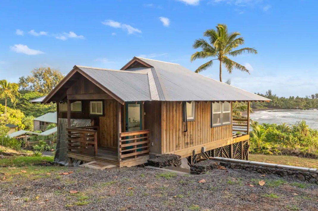 The exterior view of a wooden cottage on the edge of a beautiful tropical bay one of the best airbnbs in Hawaii