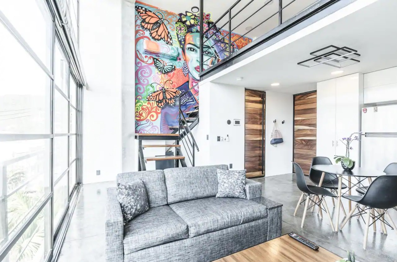 A bright and airy loft with floor to ceiling windows and a large and colorful hand painted mural of Frida Kahlo