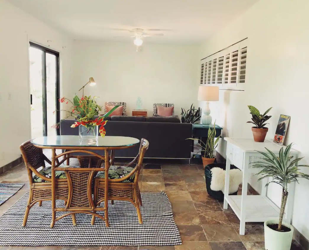 The inside of a small tropical cottage looking at a small living area with a couch, two chairs, a small dining set, and a lot of plants
