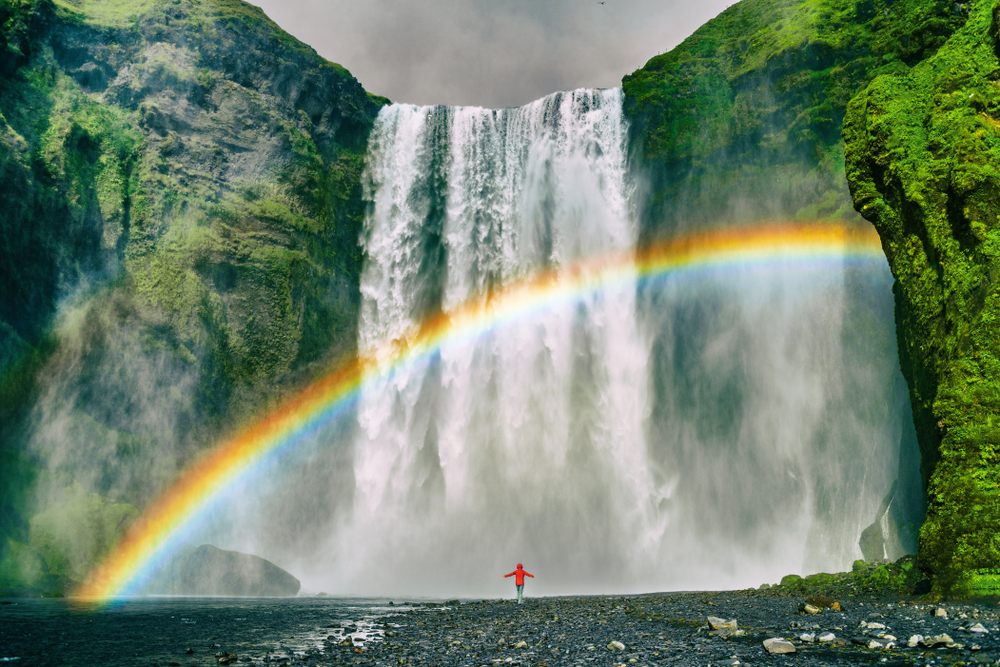 An article about rainbow quotes featuring a girl standing in front of a waterfall.