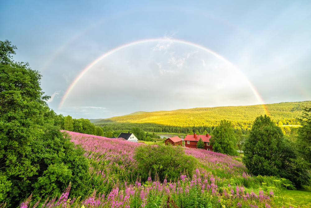 A rainbow over a field with a house in the background in a article about rainbow quotes