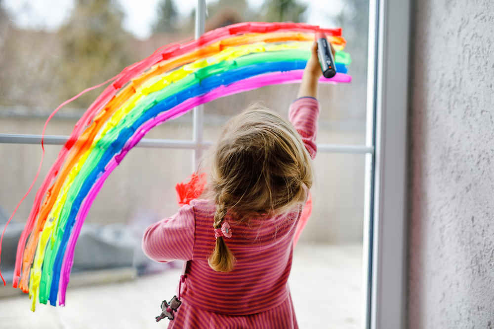 A child drawing a rainbow on a window