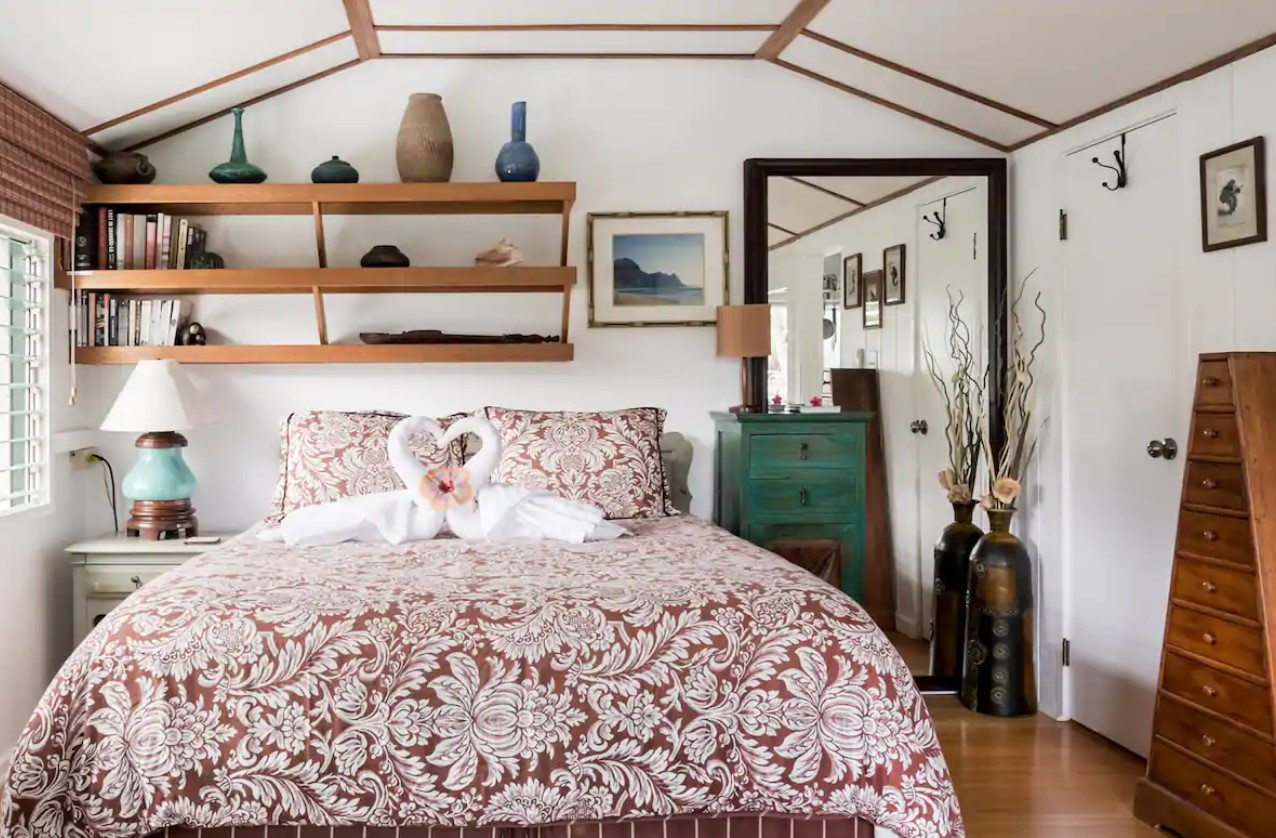 The inside of a cottage looking at the bedroom space with a queen sized bed and mid century modern shelves and furniture