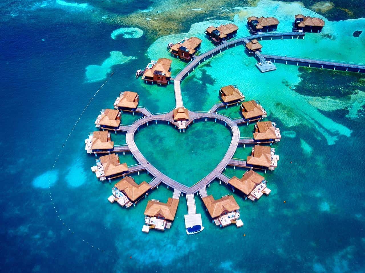A group of overwater bungalows in the shape of a heart