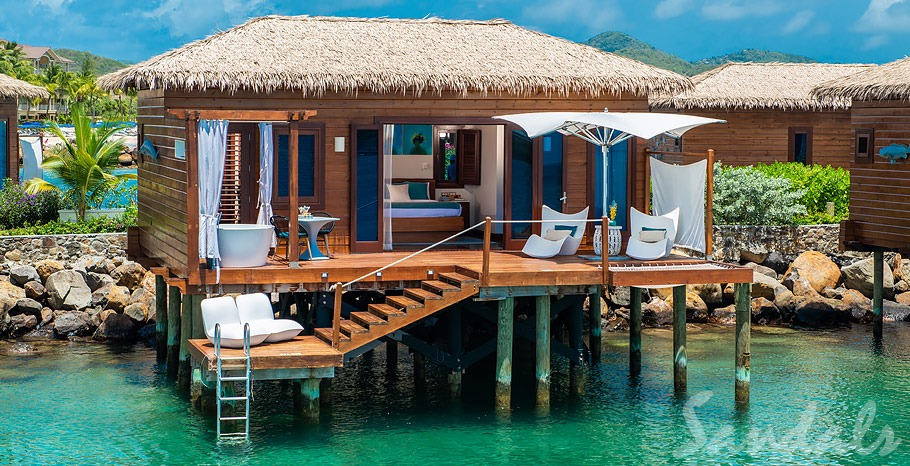 A large overwater bungalow with a private deck that has a large tub, sun loungers, a bistro set, and direct access to the ocean