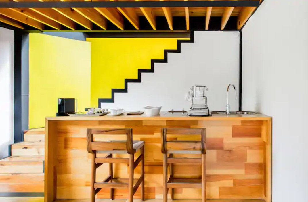 A bright yellow wall behind an open stair case that has black trim and a white wall for a striking contrast with a small bar and full kitchen made out of cedar wood in front of it airbnbs in mexico