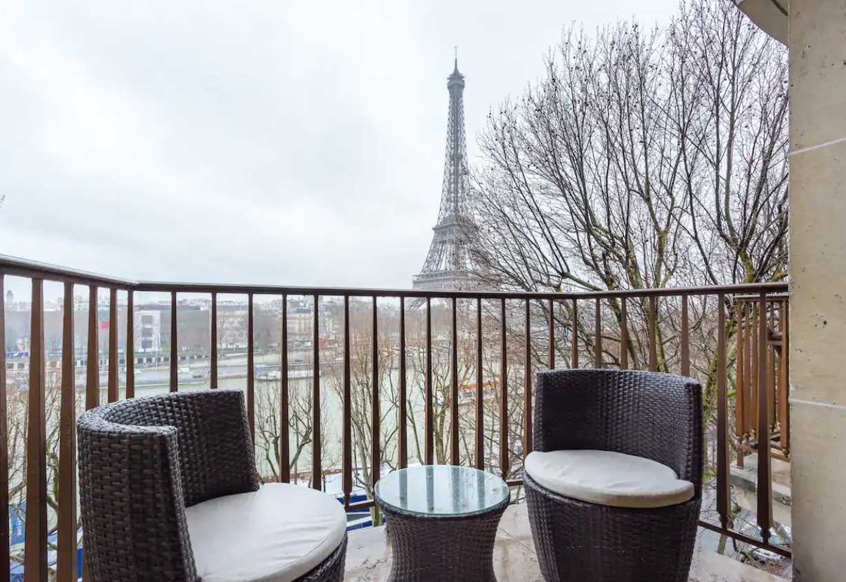 A private balcony with a small sitting area that overlooks the Seine River and the Eiffel Tower in Paris