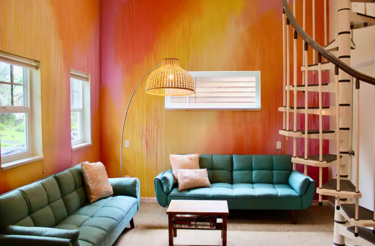 The living room of a townhouse with walls that have been painted like a watercolor in shades of orange, yellow, and pink with teal couches and a white and wood spiral staircase