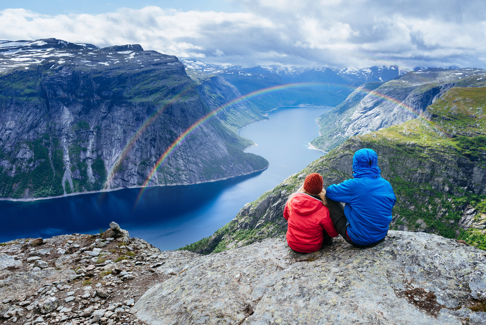 A couple sat at the top of a mountain looking down on a rainbow. Rainbow quotes can be romantic too