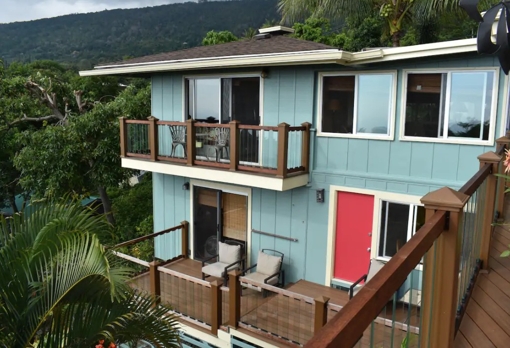 The exterior of a home on the side of a hill in the tropical rainforest of the Big Island in Hawaii with two large lanais