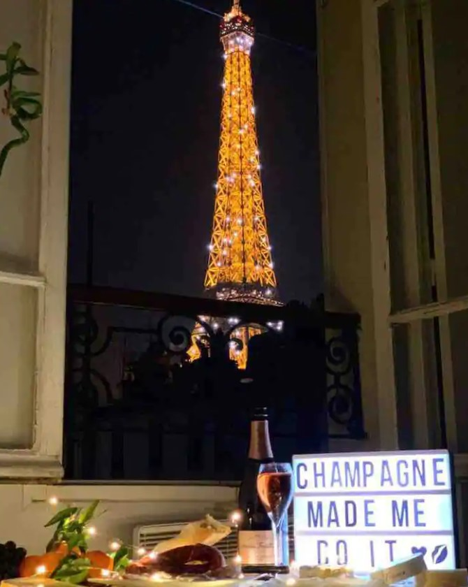 The view of the Eiffel Tower at night through and open window with a small table set up in front of it with champagne and food on it