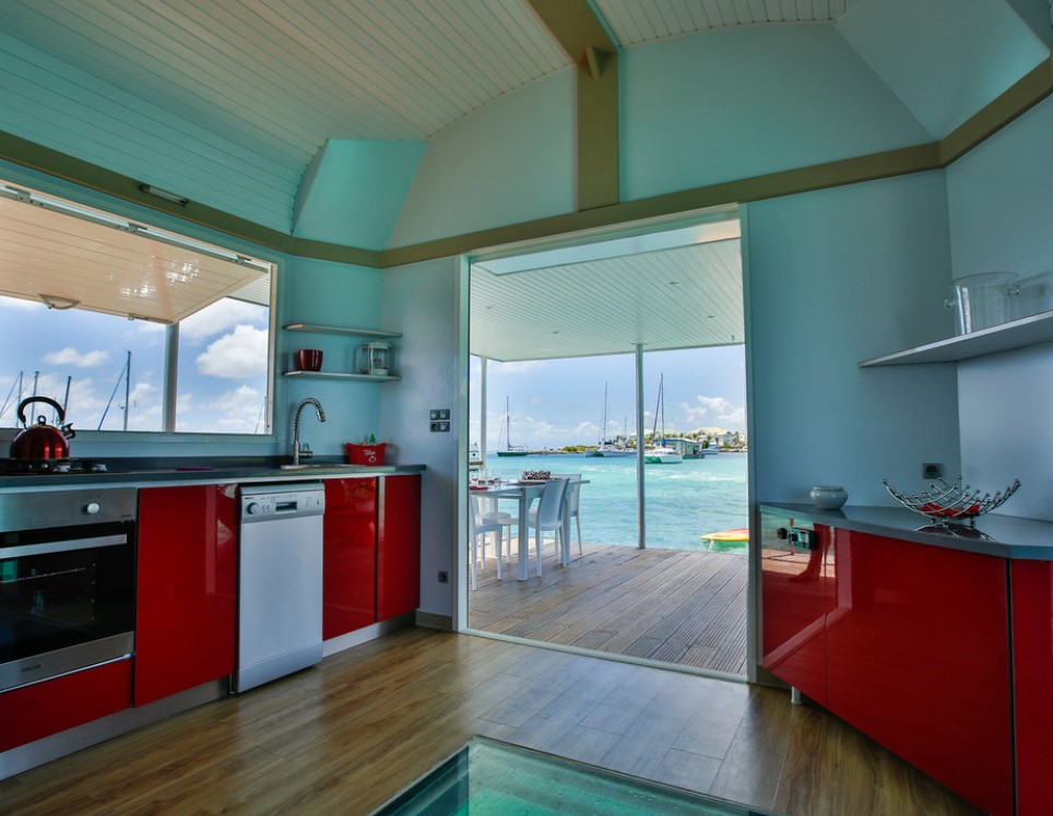 An open air kitchen with a glass floor in on an overwater bungalow in the Caribbean