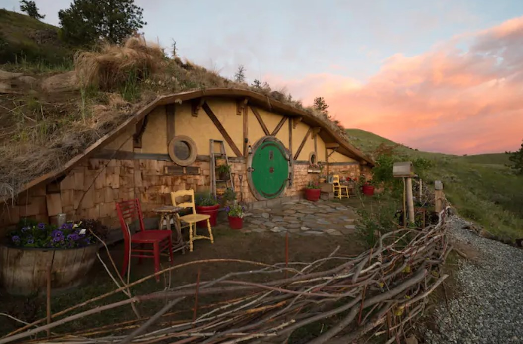 A Hobbit Hole inspired Earth house that is built into the side of a mountain with a pale yellow exterior and a large circular kelly green door best Airbnbs in Washington