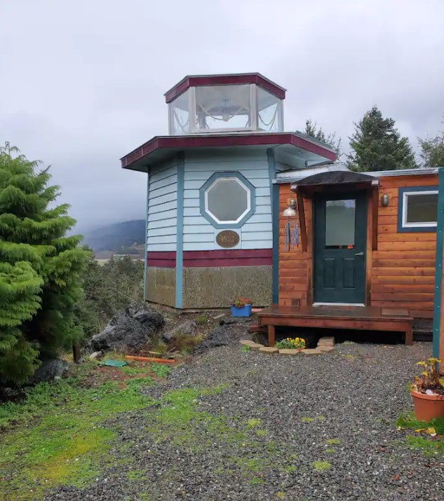 A tiny home on the side of a mountain near the pacific ocean that has part of it shaped like a lighthouse