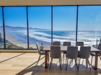 a dining room with floor to ceiling windows that look out to the Pacific Ocean