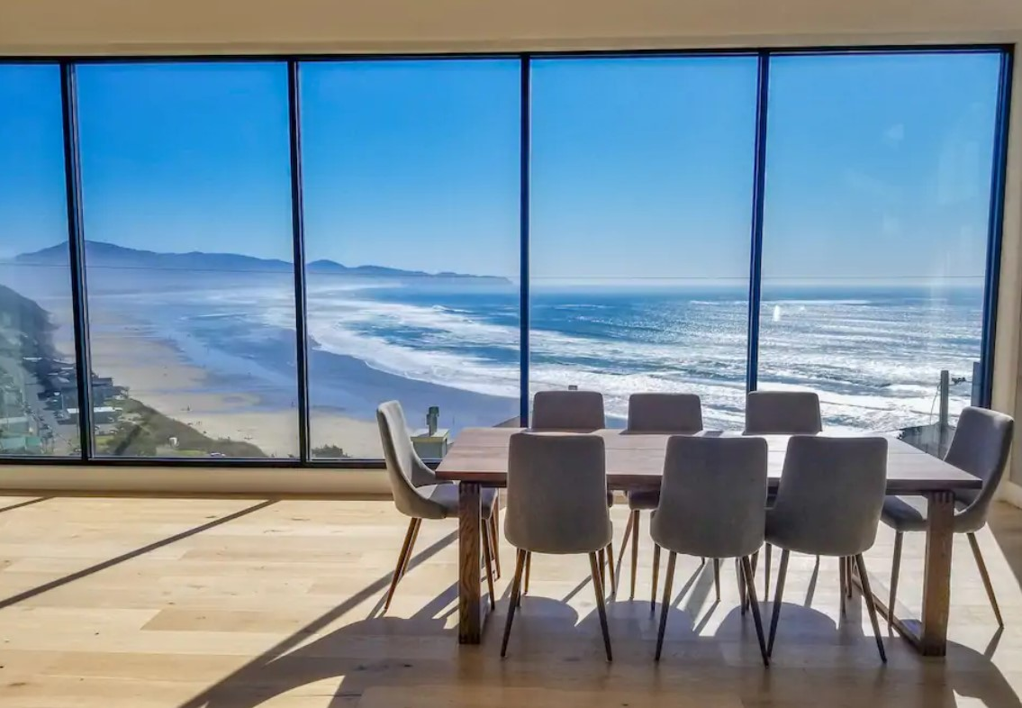 The dining room of a luxury home with floor to ceiling windows that look out onto the Pacific Ocean