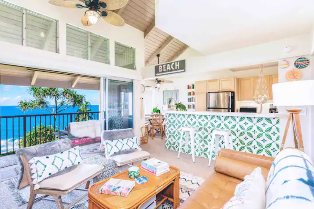 The interior view of a condo with views of the pacific ocean and eclectic boho decorations in Kauai Hawaii