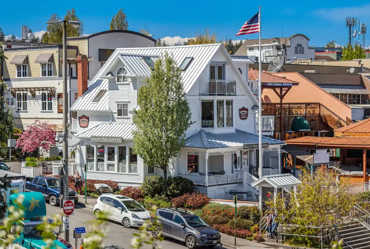 A large white Victorian house in the middle of a cute city on San Juan Island in Washington