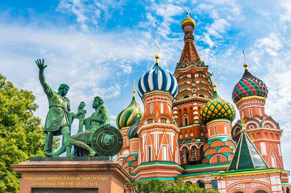 St. Basil's Cathedral in Moscow Russia with its many colorful spires and a copper sculpture in front of it on a sunny day