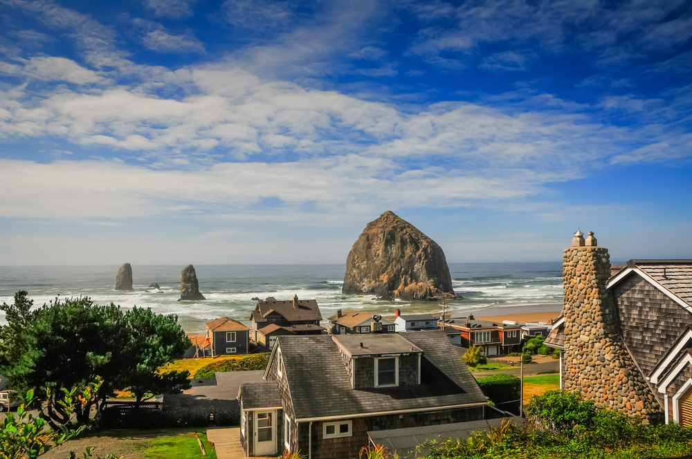 Homes on the beach in Cannon Beach Oregon where there are large rock formations in the water