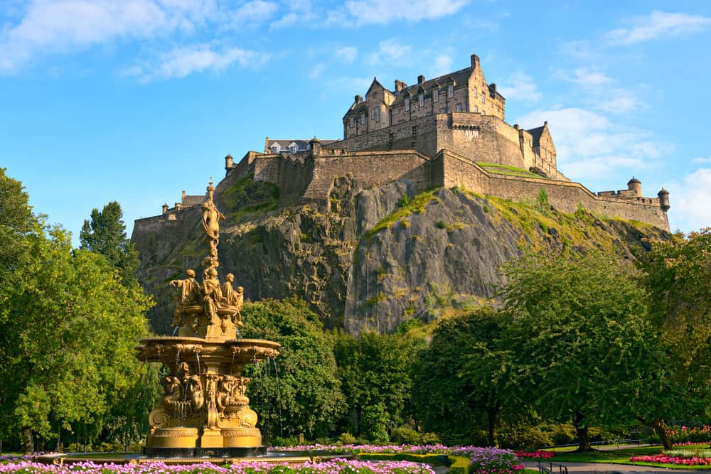 The Edinburgh Castle in Edinburgh Scotland on a large hill surrounded by greenery, trees, and with a decorative fountain in the foreground