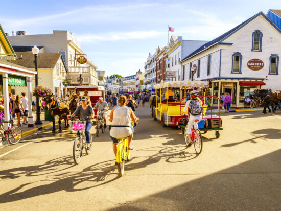 people biking on the streets of Mackinac Island one of the best small town beaches in the usa