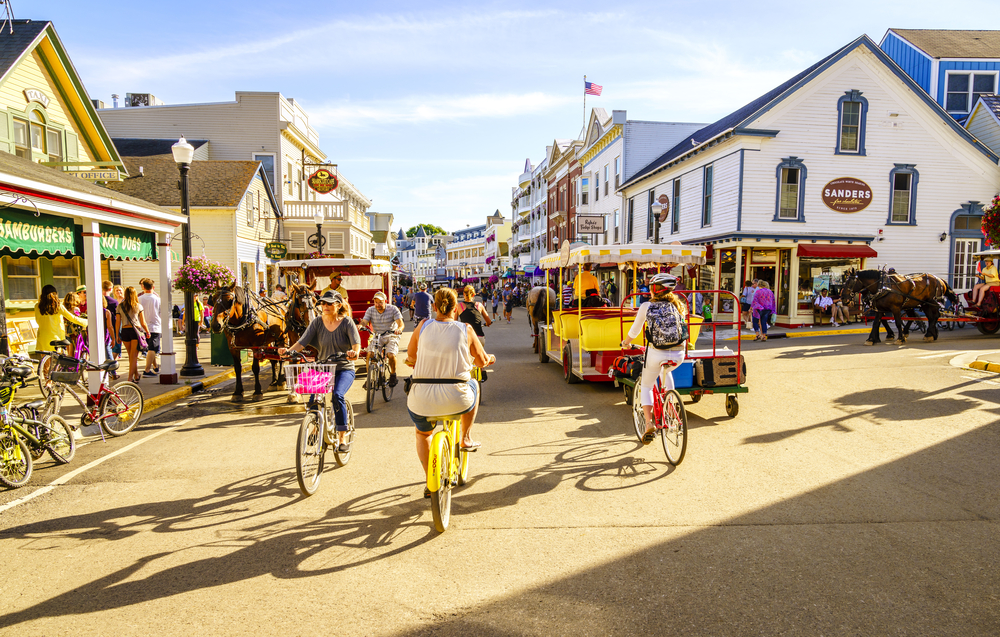 A busy street with people riding bikes, a small trolley, and horse drawn carriages on Mackinac Island in Michigan best small beach towns in the usa