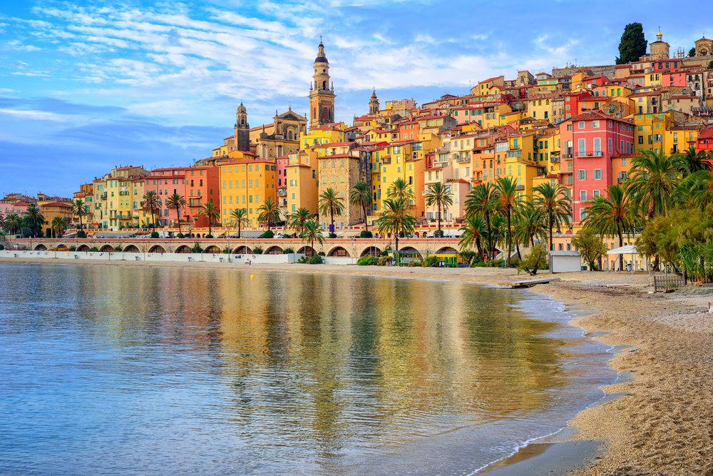 The coastal city of Menton in the French Riviera on a sunny day with colorful buildings and the Atlantic ocean