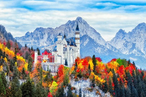 The Neweschenstein Castle in Romantic Southern Germany in the fall with the leaves changing colors and snow on the mountain tops