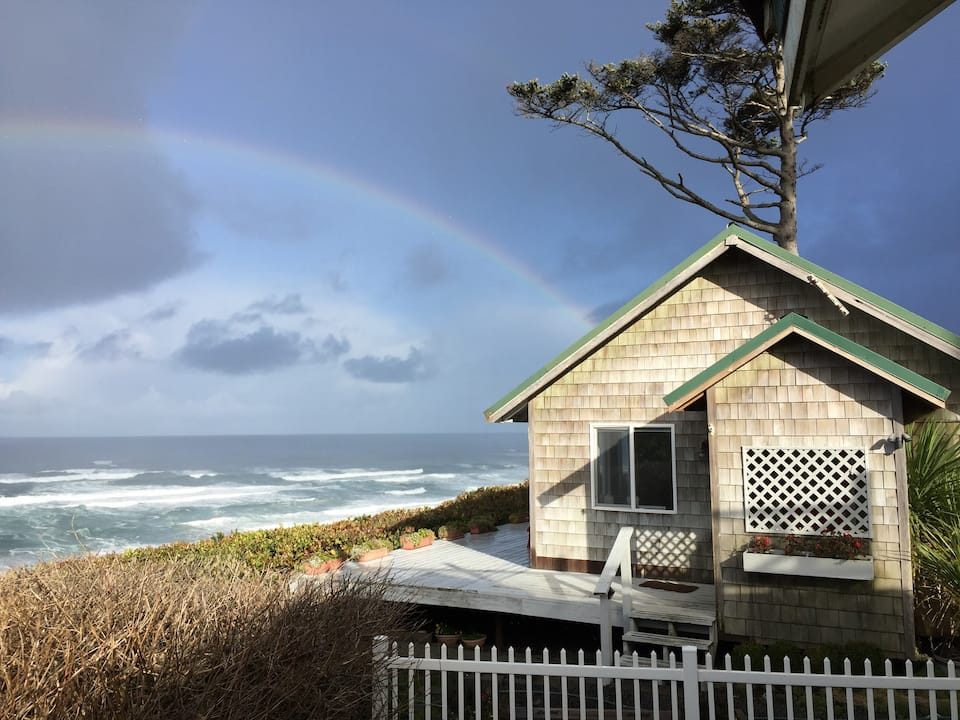 A cute cottage directly on the beach with stunning ocean views and a rainbow in the sky.