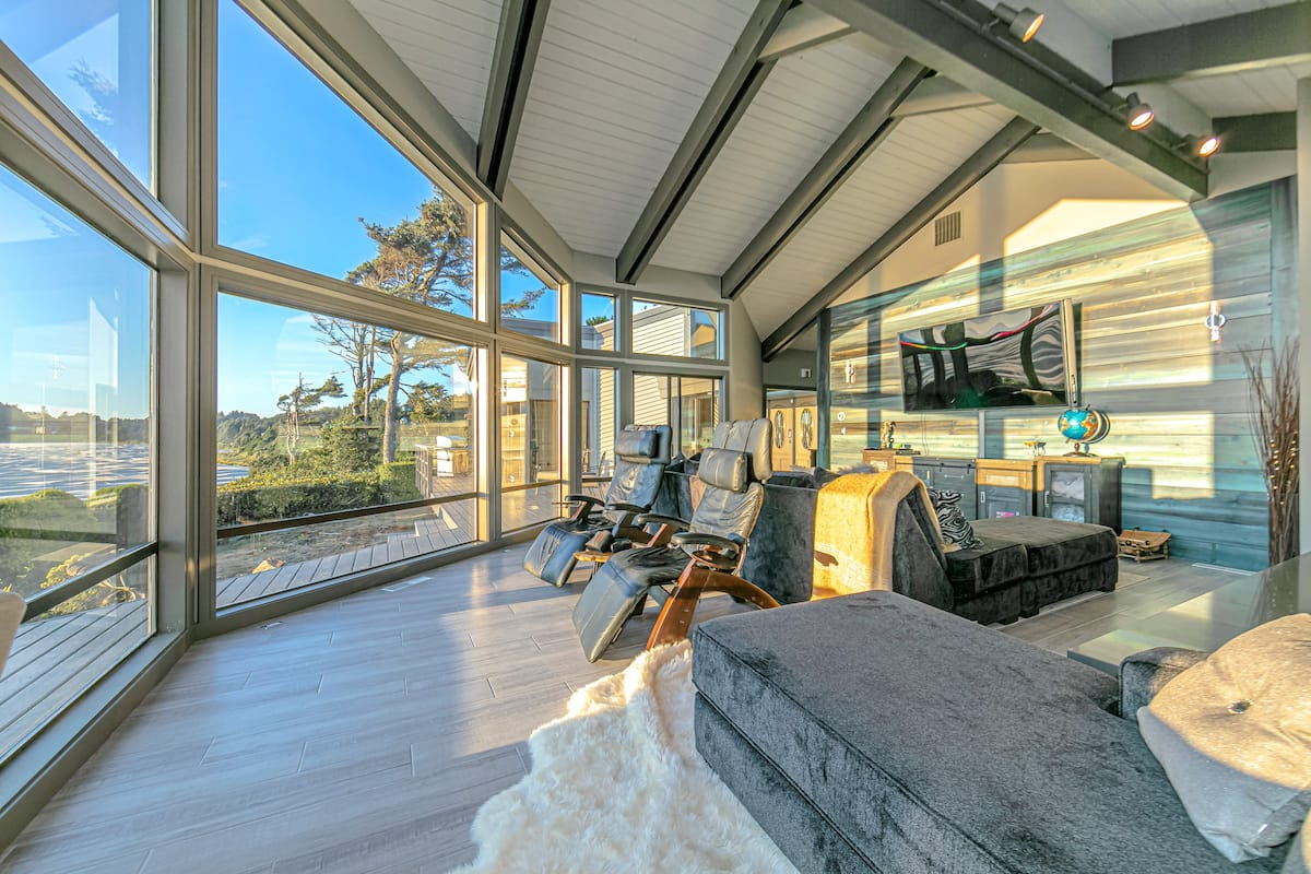 A large great room with plenty of seating that faces out to the floor to ceiling windows with views of the Pacific Ocean