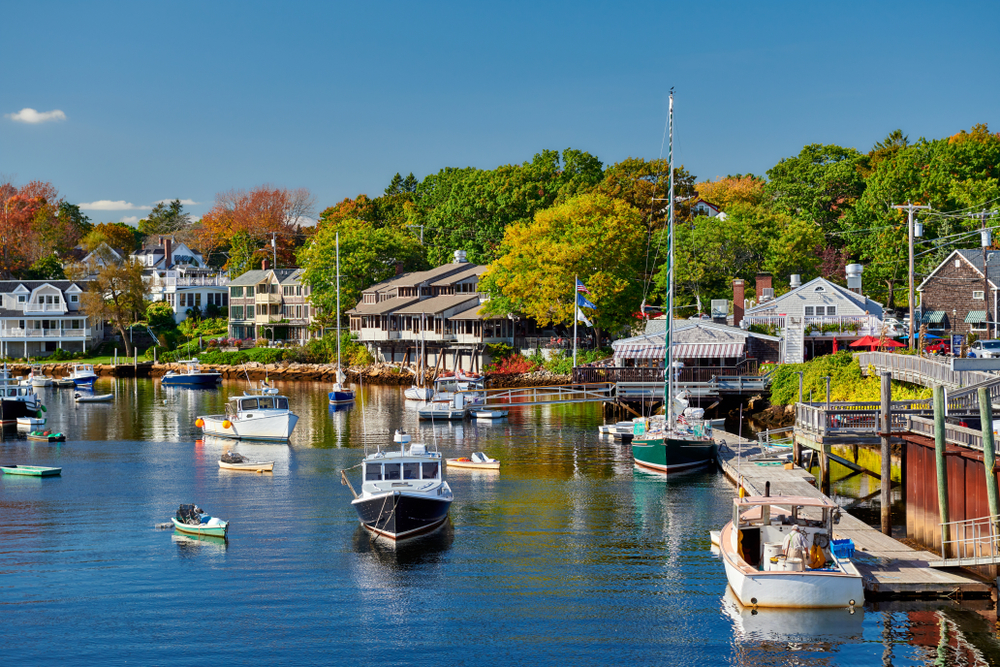 A marina surrounded by homes and trees and full of sail boats and yachts in Ogunquit Main best small beach towns in the usa