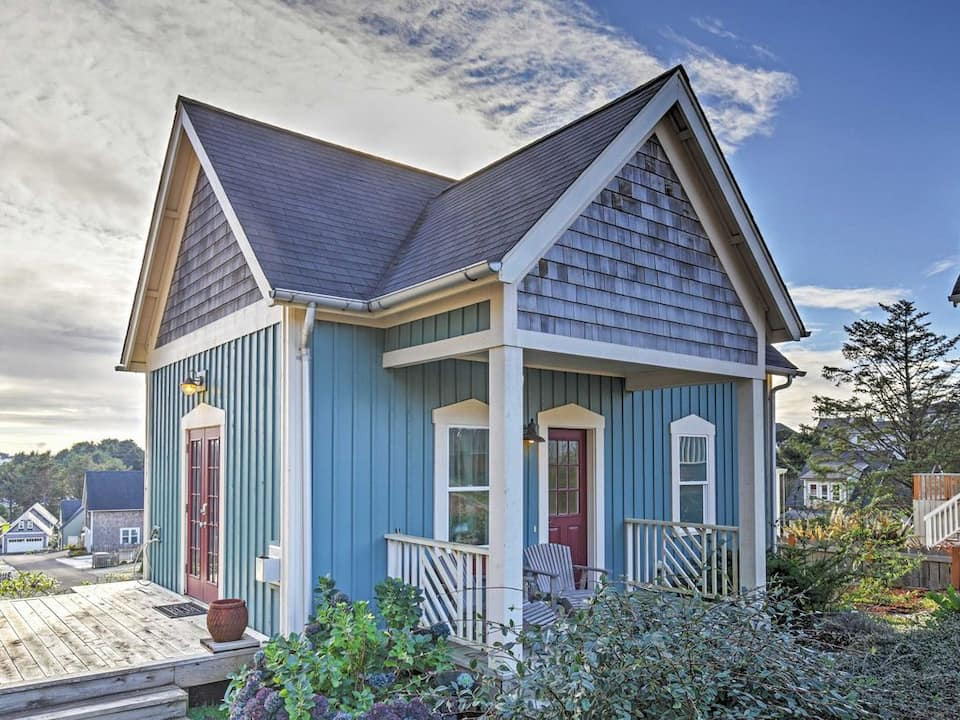 A blue tiny home with red doors, a small front porch and a larger deck off the side on the Oregon Coast